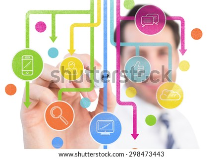 Smiling businessman writing with black marker against apps