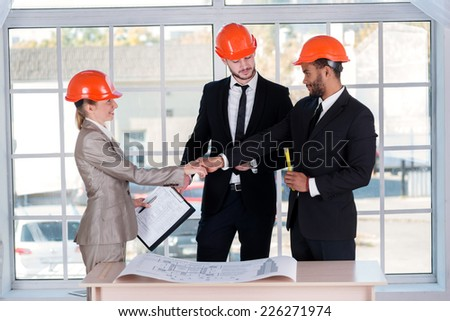 Smiling businessmen architects shaking hands. Three businessman architect met in the office to discuss business projects. Successful young people in the construction helmets are on the table
