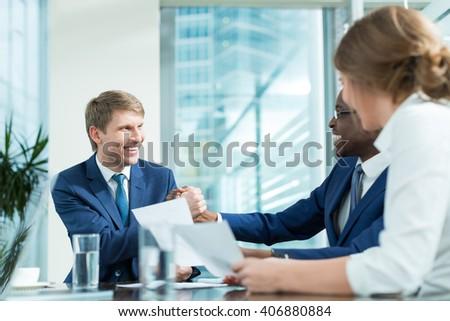 Smiling businessmen in office - stock photo
