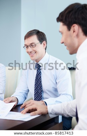 Smiling businessmen in office - stock photo