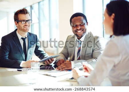 Smiling businessmen listening to young female during interview