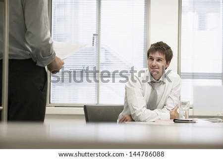 Smiling businessmen sitting in office chair and listening to male colleague - stock photo