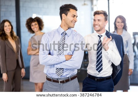 Smiling businessmen standing in front while businesswomen standing behind them in office