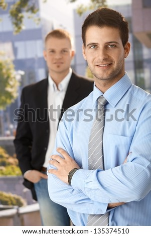 Smiling businessmen standing outside of office, looking at camera. - stock photo