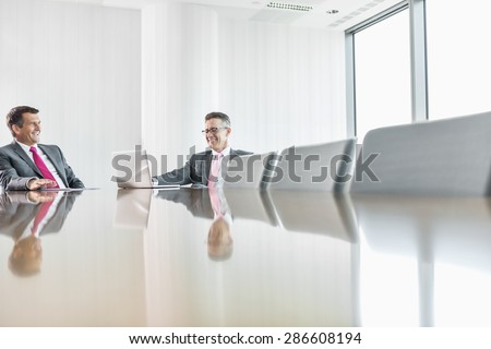 Smiling businessmen talking in conference room - stock photo