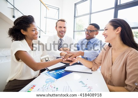 Smiling businesspeople putting their hands together during a meeting in office