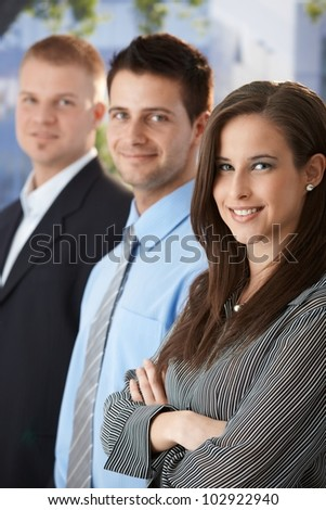 Smiling businesspeople standing outdoors, looking at camera.