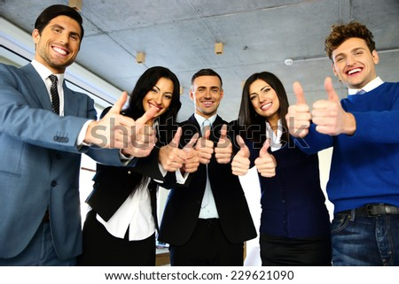 Smiling businesspeople standing with thumbs up in office - stock photo