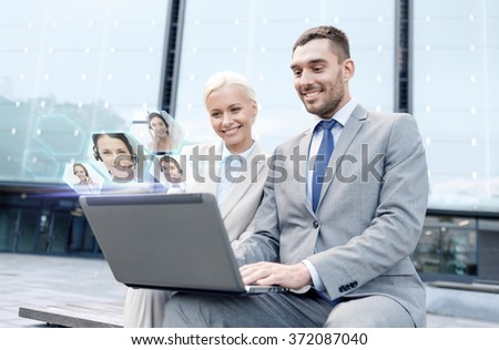 smiling businesspeople with laptop outdoors - stock photo