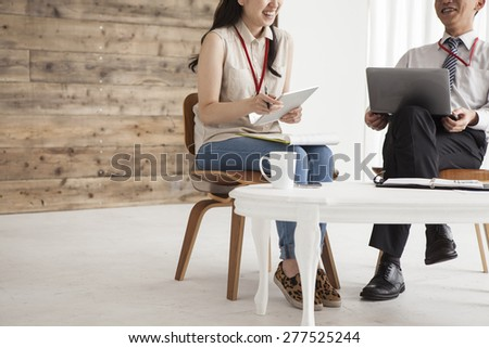 Smiling businesspeople working with laptop in office - stock photo
