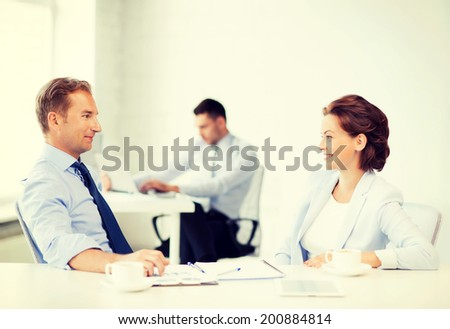 smiling businesswoman and businessman discussing something in office - stock photo