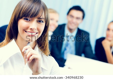 Smiling businesswoman and colleagues on background, at office - stock photo