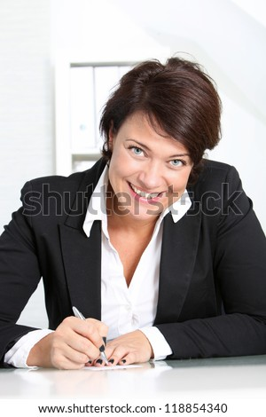 Smiling businesswoman at her desk looking up at the camera as she writes a short memo to herself - stock photo