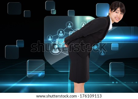 Smiling businesswoman bending against futuristic technology interface