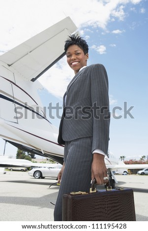 Smiling businesswoman carrying briefcase - stock photo
