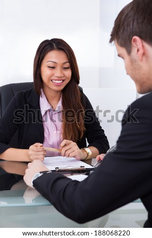 Smiling businesswoman discussing over document with male colleague in office