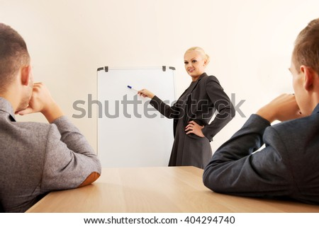 Smiling businesswoman drawing a graph for her colleagues on the whiteboard - stock photo