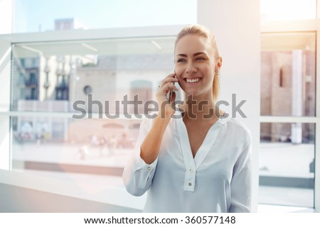 Smiling businesswoman dressed in formal wear having pleasant conversation on mobile phone with friend, happy attractive female speaking on cell telephone while resting in  office interior after work - stock photo