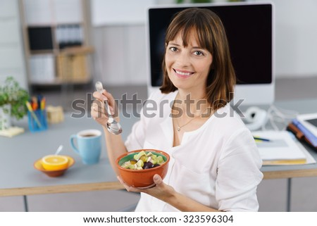Smiling businesswoman enjoying a healthy fruit salad as she sits at her desk in the office during her lunch break - stock photo