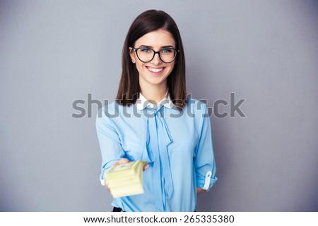 Smiling businesswoman giving money on camera over gray background. Wearing in blue shirt and glasses. Looking at camera - stock photo