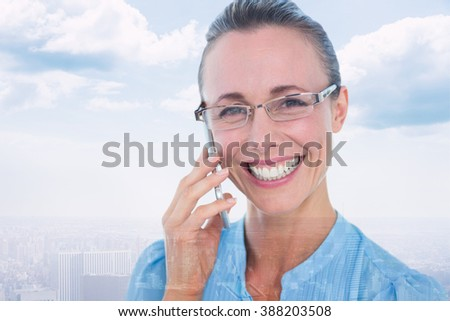 Smiling businesswoman having a phone call against city skyline - stock photo