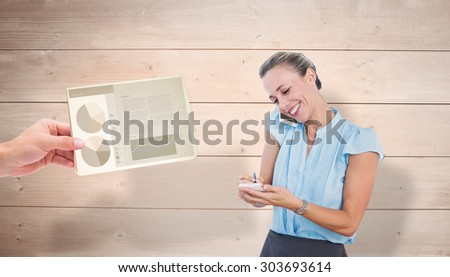 Smiling businesswoman having a phone call and taking notes against overhead of wooden planks - stock photo