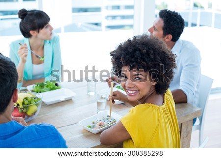 Smiling businesswoman having lunch with her colleagues - stock photo