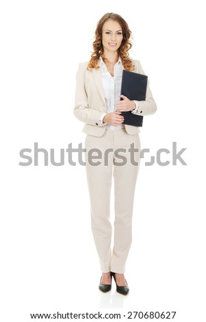 Smiling businesswoman holding a clipboard.