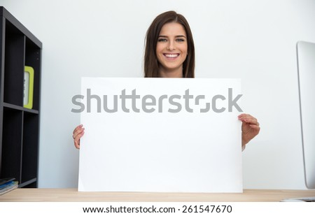 Smiling businesswoman holding blank card in office - stock photo
