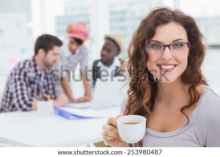 Smiling businesswoman holding cup of coffee with colleagues behind her