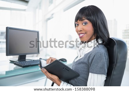 Smiling businesswoman holding datebook in bright office