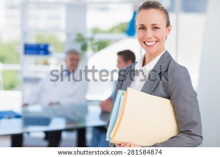Smiling businesswoman holding files and looking at camera in medical office - stock photo