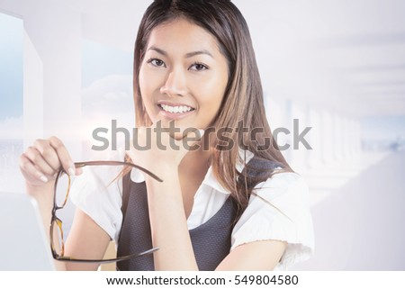 Smiling businesswoman holding her chin and her eyeglasses against bright white room with columns