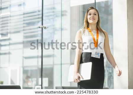 Smiling businesswoman holding laptop while standing in office - stock photo