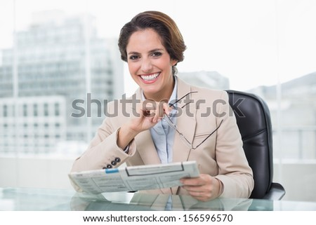 Smiling businesswoman holding newspaper in bright office - stock photo
