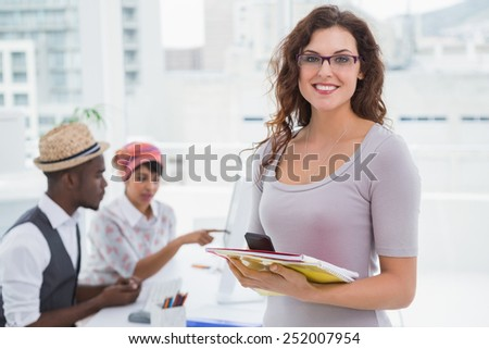 Smiling businesswoman holding phone and notebook with colleagues behind her - stock photo