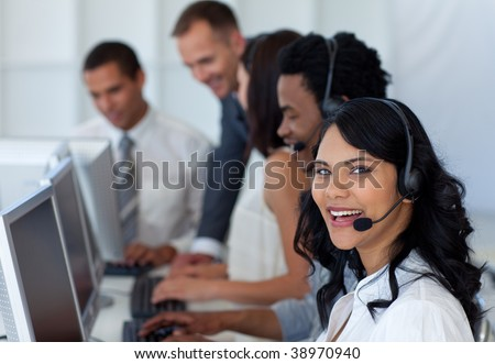 Smiling businesswoman in a call center with her multi-ethnic team
