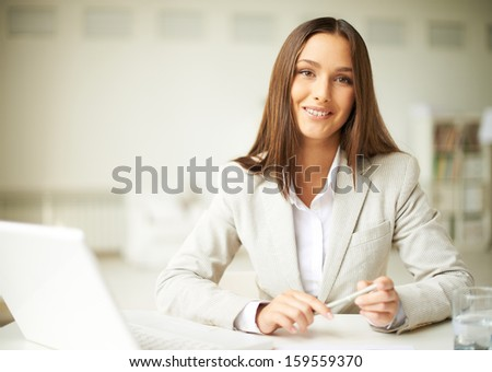 Smiling businesswoman in formalwear looking at camera - stock photo