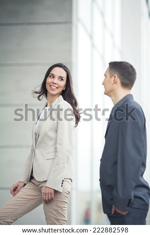 Smiling businesswoman in front of the office building with her coworker - stock photo