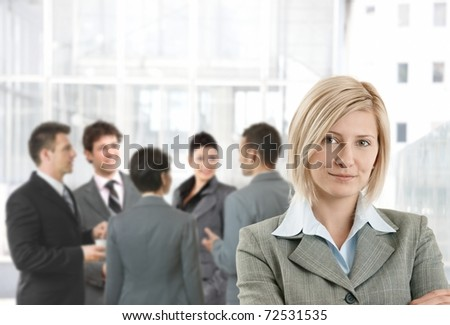 Smiling businesswoman in office lobby, colleagues talking in background.?