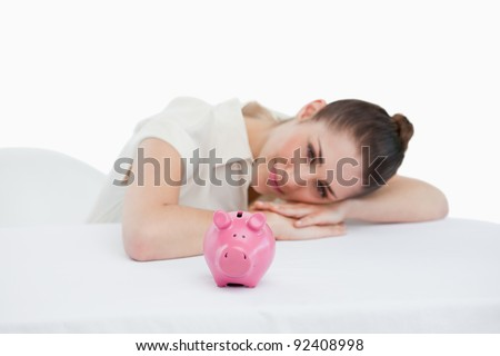 Smiling businesswoman leaning on her desk with a piggy bank against a white background - stock photo