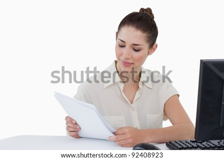 Smiling businesswoman looking a document against a white background - stock photo