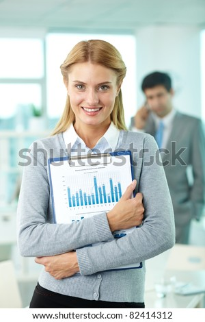 Smiling businesswoman looking at camera in working environment - stock photo