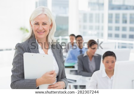 Smiling businesswoman looking at camera while work team using computer in office - stock photo