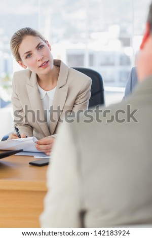 Smiling businesswoman looking at interviewee in the office - stock photo