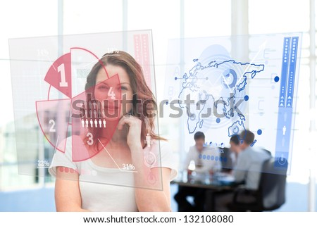 Smiling businesswoman looking at red pie chart interface with colleagues behind - stock photo