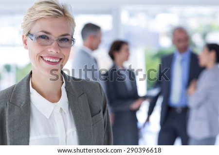 smiling businesswoman looking at the camera in the office - stock photo