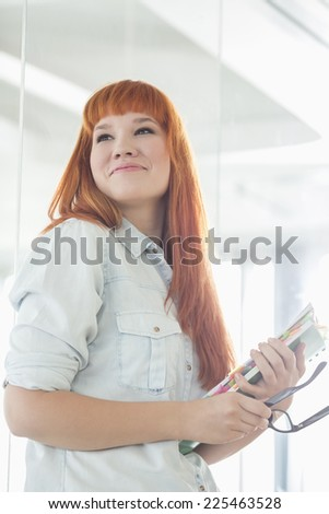 Smiling businesswoman looking away while holding files in creative office - stock photo