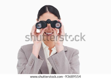 Smiling businesswoman looking through spy glasses against a white background - stock photo