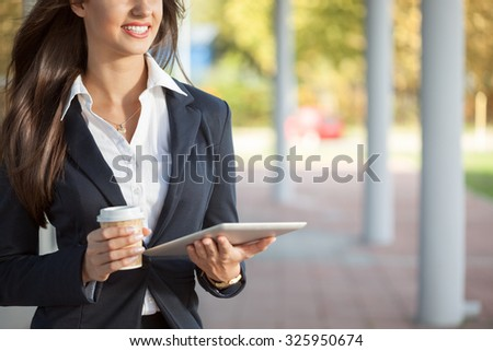 smiling businesswoman on a coffee break holding electronic tablet
